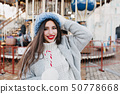 Adorable dark-haired woman spending free time in amusement park in winter weekend. Outdoor photo of 50778668