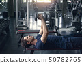 Handsome weightlifter lifting bench press working 50782765