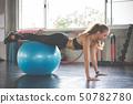 Young beautiful woman training pilates exercises 50782780