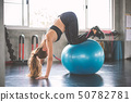 Young beautiful woman training pilates exercises 50782781