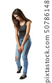 Young sad woman in sleeveless gray top and light-blue jeans standing and looking down isolated on 50786148