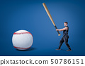Side view of young athletic man in gym suit, holding enormous bat and ready to hit huge baseball. 50786151