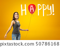 Young smiling girl in casual clothes standing in half-turn and holding red balloon against yellow 50786168