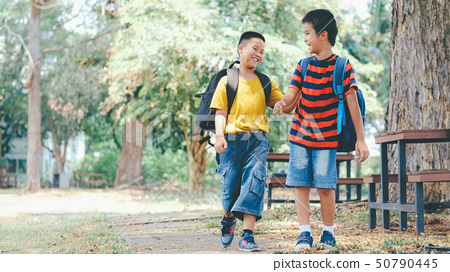 Two boys of primary with school bags behind the 50790445