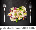 Grilled cod fillet with salad on black slate plate 50813882