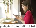 ผู้หญิงโทรศัพท์มือถือคาเฟ่ 50833844