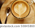 coffee cup latte art put on wooden saucer. 50845860