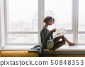 Beautiful girl sitting on big white window, reading magazine 50848353