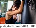 Healthy slim Caucasian female fitness sportswoman resting on punch boxing bag 50848381
