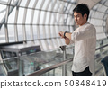 man waiting for flight and looking smart watch in 50848419