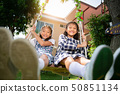 Little girl friendship playing swing together 50851134