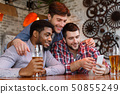 Happy Friends Watching Videos On Smartphone And Drinking Beer 50855249