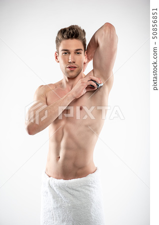 Handsome young man with perfect body applying antiperspirant on armpit 50856851