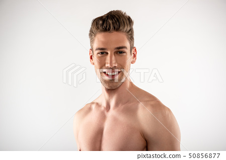 Handsome young man standing against white background 50856877
