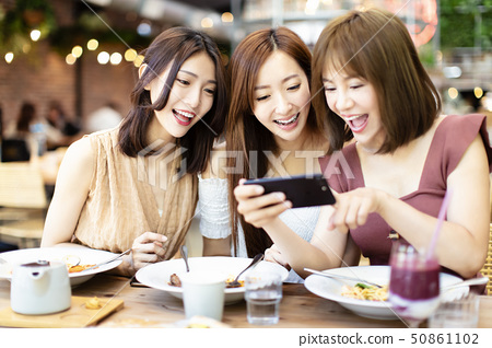 Happy friends having dinner and watching smart 50861102