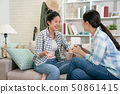 women with coffee chatting on sofa gossiping 50861415