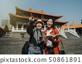 female tourists holding guide book cellphone 50861891