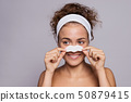 Portrait of a young woman cleaning face in a studio, beauty and skin care. 50879415