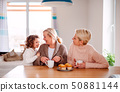 A portrait of small girl with mother and grandmother at the table at home. 50881144