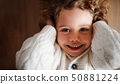 A portrait of small girl with white knitted sweater lying on the floor, a top view. 50881224