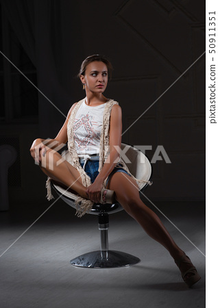 Alluring woman posing sitting on a chair. 50911351