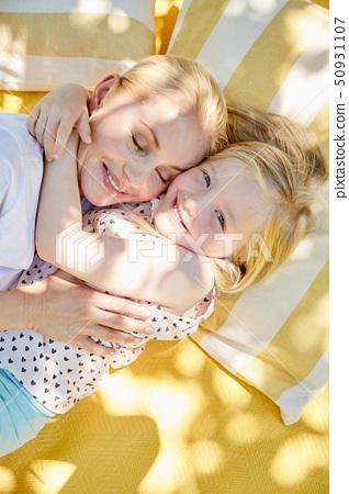 Happy girl hugging mother on a blanket 50931107