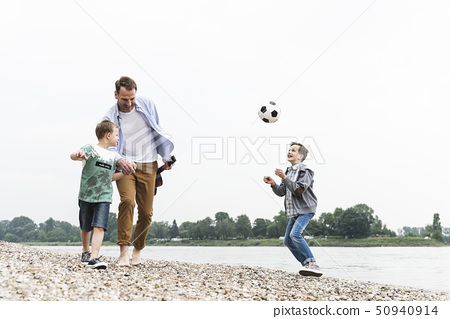 Happy father with two sons and football walking at the riverside 50940914