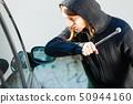 Thief burglar breaking smashing the car window 50944160
