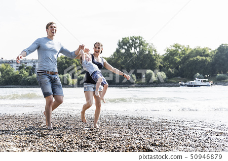 Happy family walking at the riverside on a beautiful summer day 50946879