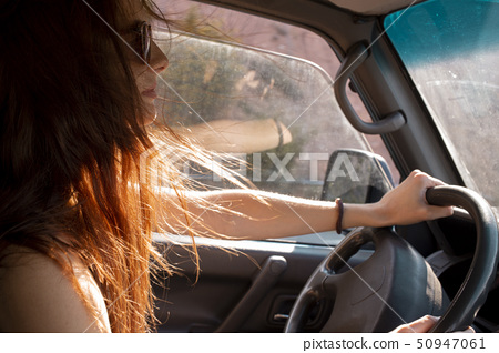 Young woman with windswept hair driving a car 50947061