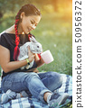 Pretty Girl With Hair Braiding Huggs a Rabbit on Beautiful Summer Nature 50956372
