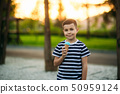 A little boy in a striped T-shirt is eating blue ice cream.Spring, sunny weather 50959124