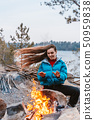 Happy young brunette girl sitting next to bonfire 50959838
