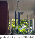 Wind chime on a red brick house with white pillars 50963441