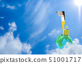 Young Woman standing on earth  and looking in 51001717