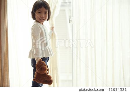작은 곰을 가지고 창가에 서 여자 51054521