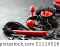Set of erotic toys for BDSM. The game of sexual slavery with handcuffs, whip, gag and leather straps 51114516