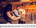 Curly woman drinking cocktail in bar talking to man 51121439