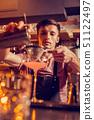 Barman wearing balk apron making cocktail with juice 51122497
