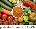 Uncookes brown millet in a bowl with vegetables 51145497