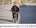 chimpanzee monkey ride bicycle on street 51151828