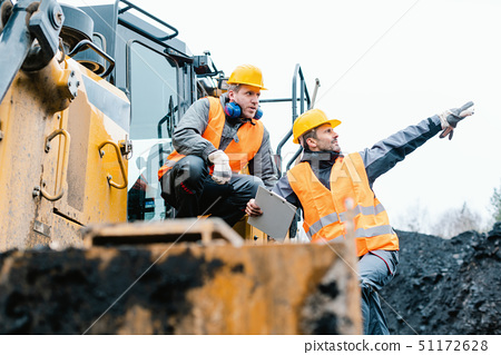 Foreman showing worker in open-cast mining pit direction 51172628