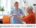 Pleasant female nurse looking at her patient 51186832