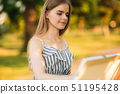 Portrait of Blond hair girl in dress drawing a picture in the park 51195428