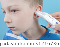 taking temperature with ear thermometer by child 51216736