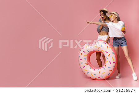 Emotional females pointing at empty space, standing with inflatable ring o 51236977