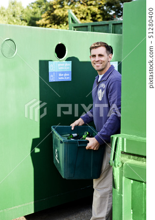 A mid-adult man recycling glass bottles 51280400