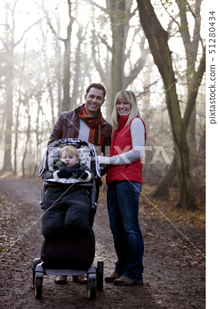 A young couple pushing a stroller in the park, smiling 51280434