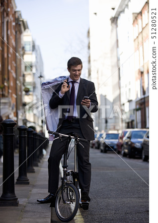 A businessman on his bicycle, looking at his phone 51280521