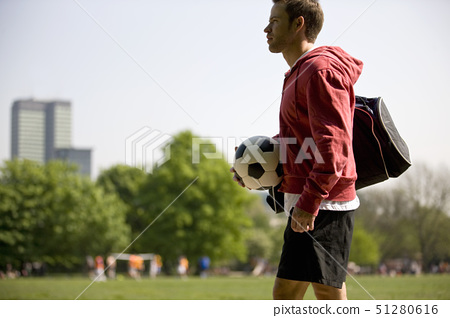 A young man standing in the park, carrying a football and a sports bag 51280616